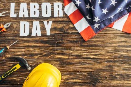 vista superior de la bandera americana cerca de instrumentos, casco de seguridad y letras del día del trabajo en la superficie de madera