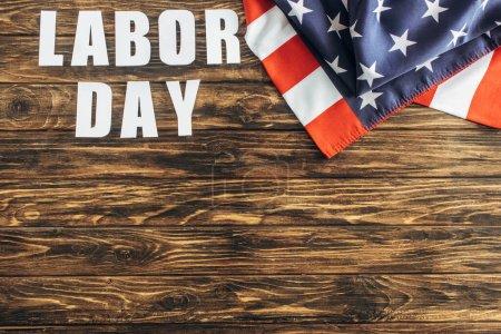 Photo pour Vue du dessus du drapeau américain près du lettrage de la fête du travail sur la surface en bois - image libre de droit