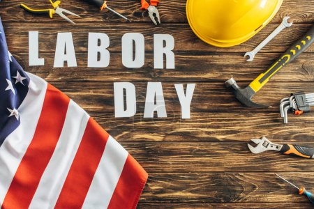 Photo for Top view of american flag near tools, safety helmet and labor day lettering on wooden surface - Royalty Free Image