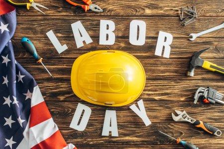 Photo pour Vue du dessus des outils, casque de sécurité et drapeau américain près du lettrage de la fête du travail sur la surface en bois - image libre de droit