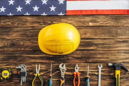 top view of metallic tools, safety helmet and american flag on wooden surface, labor day concept