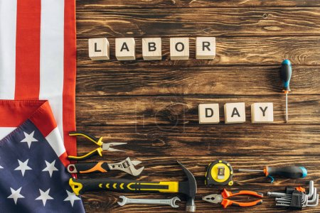 Photo for Top view of metallic tools and american flag near cubes with labor day lettering on wooden surface - Royalty Free Image