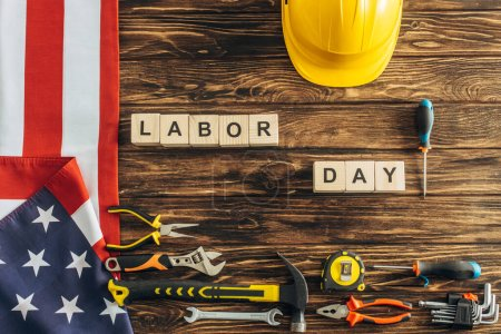 Photo for Top view of interments, safety helmet and american flag near cubes with labor day lettering on wooden surface - Royalty Free Image