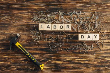 Photo for Top view of metallic nails and hammer near cubes with labor day lettering on wooden surface - Royalty Free Image