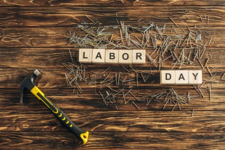 Photo for Top view of metal nails and hammer near cubes with labor day lettering on wooden surface - Royalty Free Image