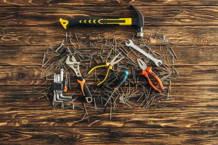 Photo for Top view of tools and metallic nails on wooden surface, labor day concept - Royalty Free Image