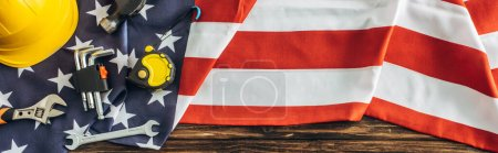 panoramic crop of instruments and safety helmet on american flag, labor day concept