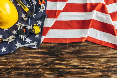 Photo for Top view of instruments and safety helmet on american flag and wooden surface, labor day concept - Royalty Free Image