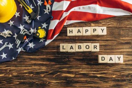 Photo pour Vue de dessus du casque de sécurité et des instruments près du lettrage heureux de jour de travail près du drapeau américain sur la surface en bois - image libre de droit