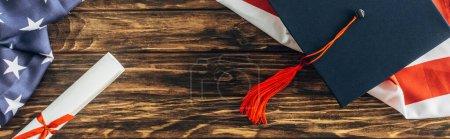 Photo pour Recadrage horizontal de casquette graduée et diplôme près du drapeau américain avec des étoiles et des rayures sur la surface en bois - image libre de droit