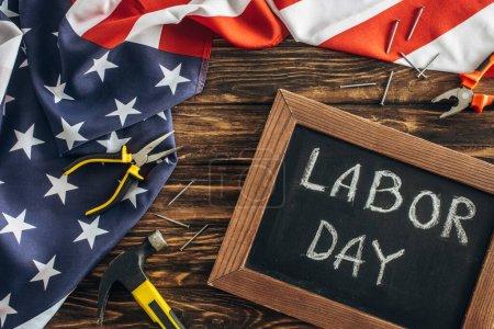 Photo pour Vue de dessus du drapeau américain, des clous métalliques et des instruments près du tableau avec le lettrage de jour de travail sur la surface en bois - image libre de droit