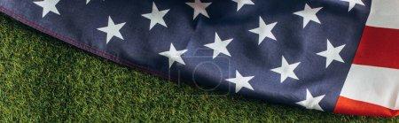 horizontale Ernte der amerikanischen Flagge mit Sternen und Streifen auf grünem Gras draußen, Arbeitszeitkonzept