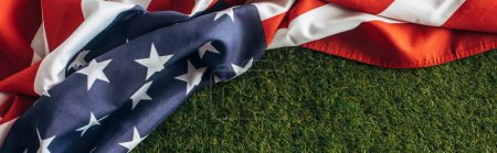 Photo for Horizontal image of american flag with stars and stripes on green grass outside, labor day concept - Royalty Free Image