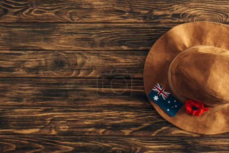Photo for Top view of felt hat, artificial flower and australian flag on wooden surface, anzac day concept - Royalty Free Image