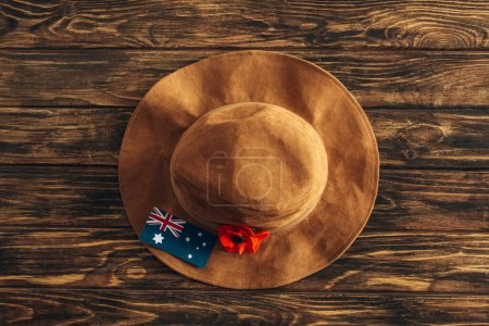 top view of artificial flower, felt hat and australian flag on wooden surface, anzac day concept