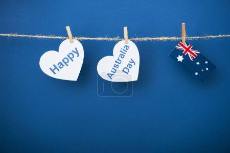 Photo pour Corde, pinces à linge et papiers en forme de coeur avec joyeux lettrage de jour près de l'Australie et drapeau sur bleu - image libre de droit