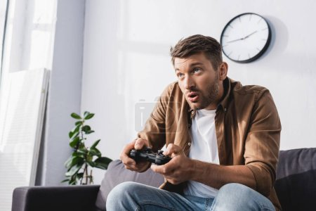 Photo for KYIV, UKRAINE - JUNE 9, 2020: excited man playing video game with joystick at home - Royalty Free Image