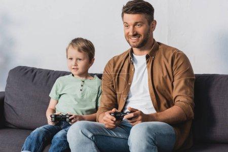 Photo pour KYIV, UKRAINE - 9 JUIN 2020 : père et fils souriants assis sur le canapé et jouant au jeu vidéo avec joystcks - image libre de droit