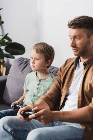 Photo pour KYIV, UKRAINE - 9 JUIN 2020 : père et fils concentrés assis sur le canapé et jouant à un jeu vidéo avec des joysticks - image libre de droit