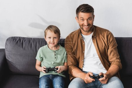 KYIV, UKRAINE - JUNE 9, 2020: excited father and son looking at camera while playing video game with joysticks