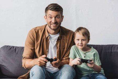 Photo pour KYIV, UKRAINE - 9 JUIN 2020 : père et fils excités assis sur le canapé et jouant à un jeu vidéo avec des joysticks - image libre de droit