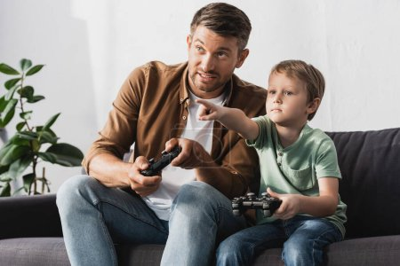Photo for KYIV, UKRAINE - JUNE 9, 2020: adorable boy pointing with finger while playing video game with father - Royalty Free Image