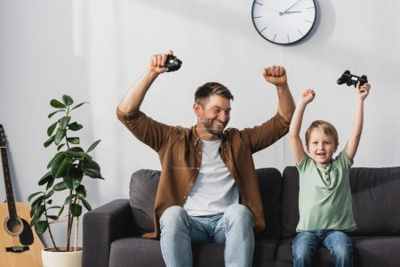 Photo for KYIV, UKRAINE - JUNE 9, 2020: happy father and son showing winner gestures while holding joysticks - Royalty Free Image