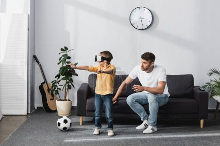 Photo for Boy in vr headset standing with outstretched hands near father sitting on sofa - Royalty Free Image