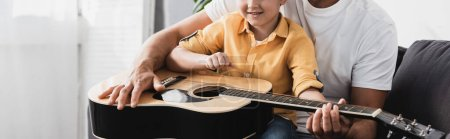 cropped view of boy sitting on fathers knees and learning how to play acoustic guitar