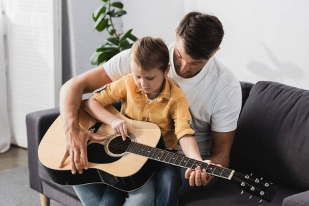 Photo for Cute boy sitting of fathers knees and learning how to play acoustic guitar - Royalty Free Image