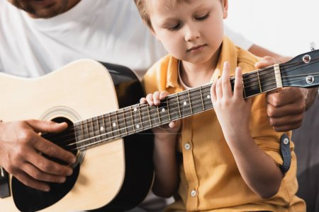 Photo for Cropped view of father teaching attentive son how to play acoustic guitar - Royalty Free Image
