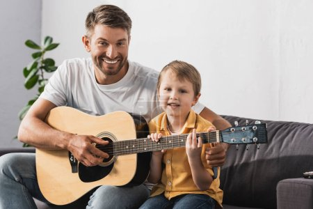 Photo for Happy father teaching cheerful son how to play acoustic guitar - Royalty Free Image