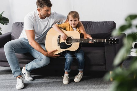 Photo pour Foyer sélectif de beau père enseignant fils comment jouer de la guitare acoustique - image libre de droit