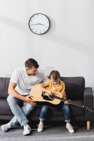 attentive boy learning how to play acoustic guitar while sitting on sofa near father