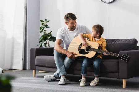 father and son looking at each other while boy learning how to play acoustic guitar