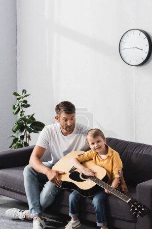 handsome father teaching son to play acoustic guitar on sofa at home