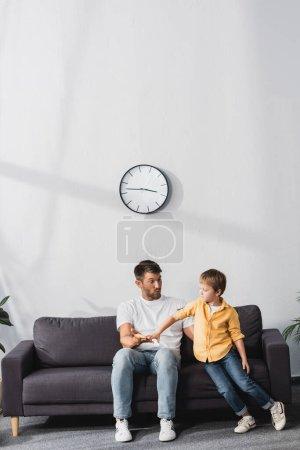 Photo pour Père et fils se tenant la main assis sur le canapé à la maison - image libre de droit