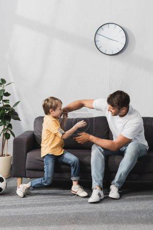Photo pour Heureux père et fils s'amuser tout en se battant avec plaisanterie sur le canapé à la maison - image libre de droit