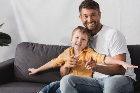 Photo pour Heureux père et fils souriant avec les mains tendues assis sur le canapé à la maison - image libre de droit