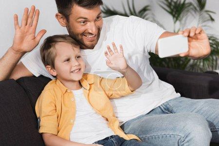 Photo pour Heureux père et fils agitant les mains dring chat vidéo sur smartphone - image libre de droit