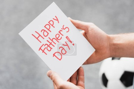 partial view of man holding happy father day card near soccer ball