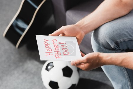 Photo for Cropped view of man holding happy father day card near soccer ball - Royalty Free Image
