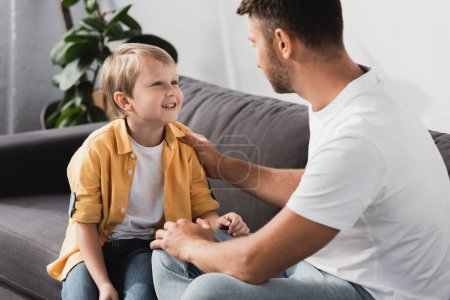 Photo pour Père touchant épaule de fils souriant tout en lui parlant sur le canapé - image libre de droit