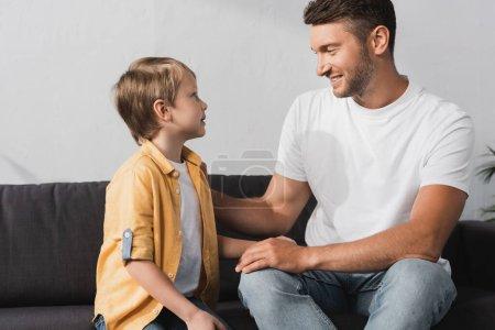 Photo pour Souriant père touchant fils mignon tout en étant assis sur le canapé et lui parlant - image libre de droit