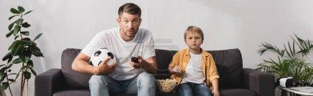 horizontales Bild eines besorgten Mannes mit Fußballball und Fernbedienung in der Nähe seines Sohnes, der Popcorn isst
