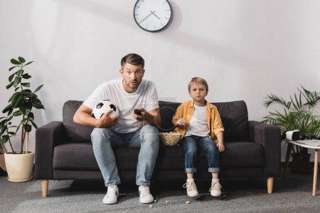 Photo pour Homme inquiet tenant ballon de football et télécommandes tv près de fils manger du maïs soufflé - image libre de droit