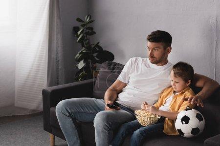 Photo pour Ennuyé père et fils regarder la télévision avec bol de pop-corn près du ballon de football - image libre de droit