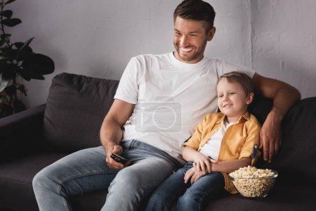 Photo pour Père souriant tenant télécommande tv et fils souriant près bol de maïs soufflé regarder la télévision à la maison - image libre de droit
