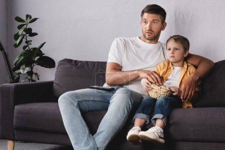 Aufmerksame Vater und Sohn fernsehen und Popcorn zu Hause auf dem Sofa essen