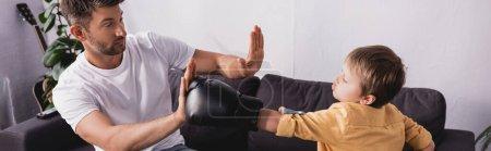 Photo pour Image horizontale du garçon en gants de boxe se battant avec son père assis sur le canapé - image libre de droit